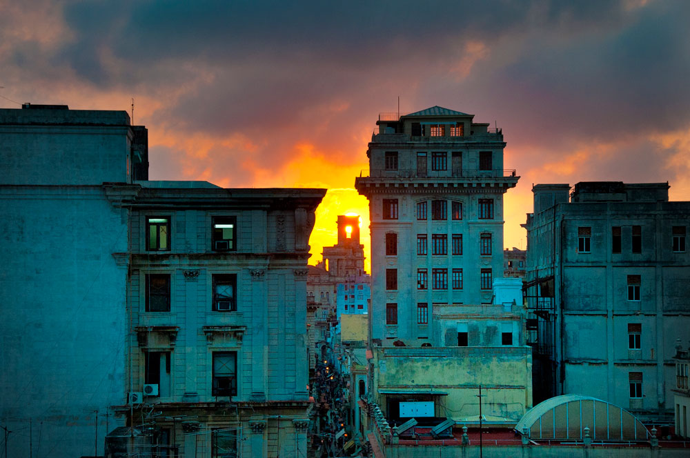 city buildings with sunset in background